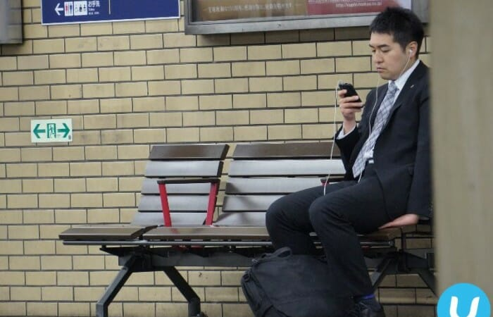 A Japanese executive texting at a subway station in Kobe.